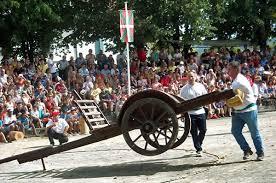 Homme soulevant une charrette pendant une féria basque.