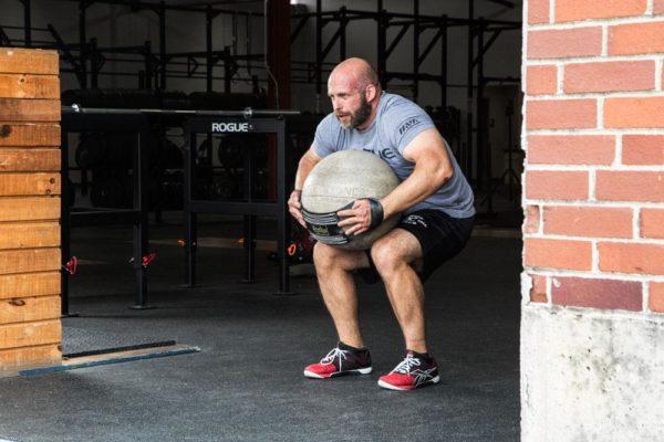 Homme en train de faire du sport, plus précisément de soulever un medecin ball.
